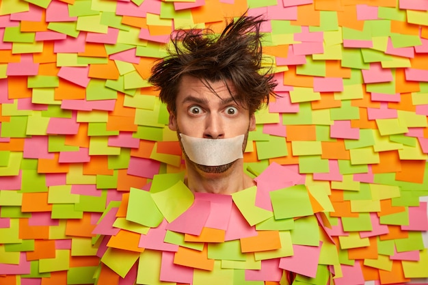 Hombre nervioso sorprendido con cinta adhesiva sobre la boca, pide silencio, se queda callado y sin palabras, posa contra la pared colorida con notas adhesivas, está asustado. cállate censura