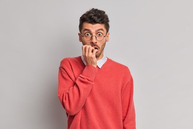 Hombre nervioso sorprendido muerde las uñas mira a través de lentes ópticos