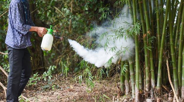 Hombre con niebla para eliminar el mosquito para prevenir la propagación de la fiebre del dengue y el virus del zika en el bambú