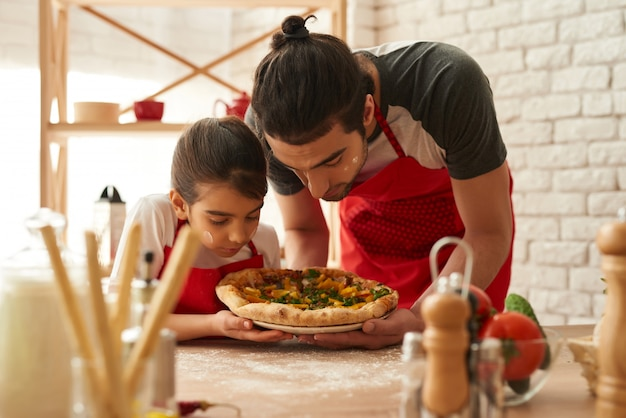 El hombre y la niña cocinaban hermosa pizza en la cocina.