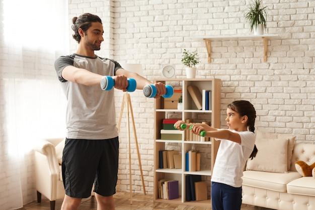 Hombre y niña haciendo ejercicios con pesas.
