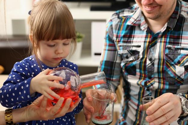 El hombre y la niña juegan con líquidos coloridos