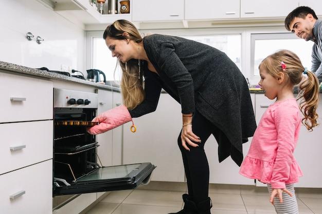 Hombre y una niña mirando a mujer hornear galletas en el horno