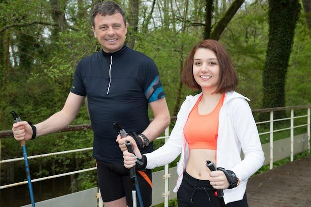 El hombre y la niña van con palos deportivos en un bosque