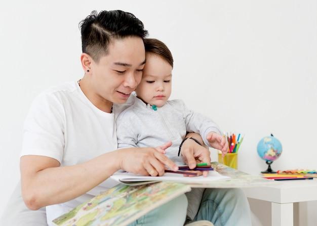 Hombre y niño dibujando juntos en casa