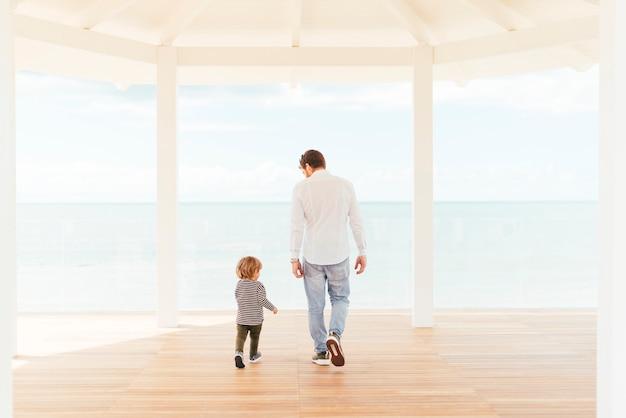 Hombre y niño pequeño caminando en el porche