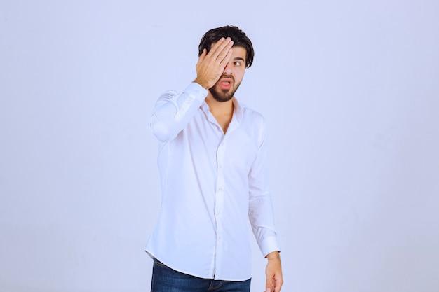 Hombre observando el exterior a través de sus dedos u ocultando su rostro.