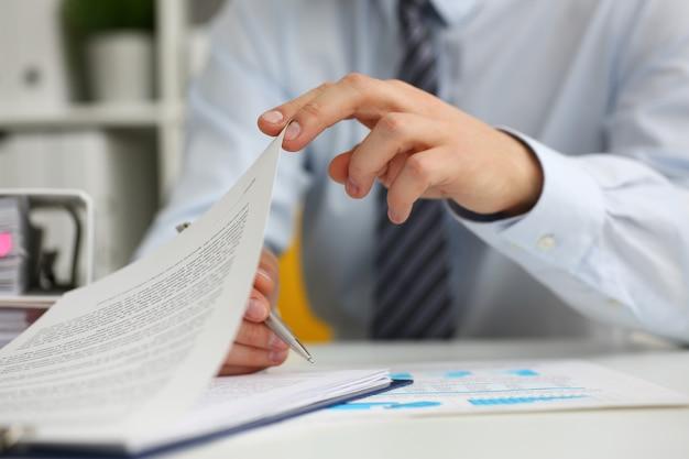 El hombre está ocupado con un contrato en su lugar de trabajo.