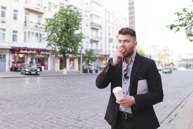 Un hombre ocupado está de pie junto a la carretera, comiendo un sándwich, tomando café y tomando un taxi.
