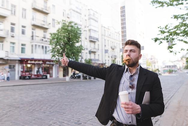 Un hombre ocupado con una taza de café en las manos y un sándwich en los dientes coge un taxi en la carretera.