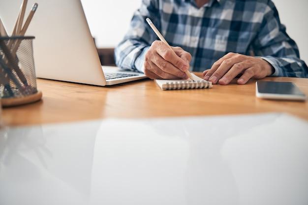 Hombre ocupado tomando notas durante la reunión en línea mientras trabaja desde su oficina en casa