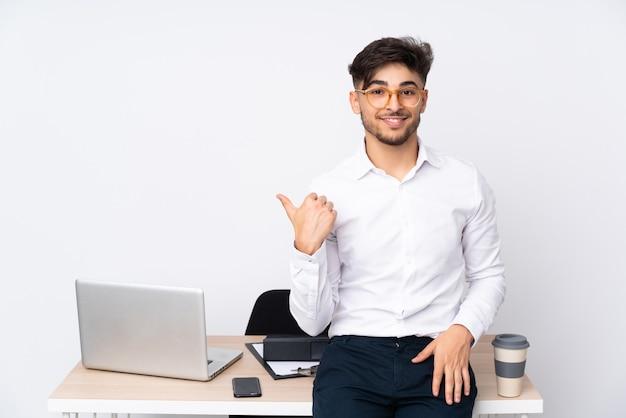 Hombre en una oficina aislada en la pared blanca apuntando hacia un lado para presentar un producto