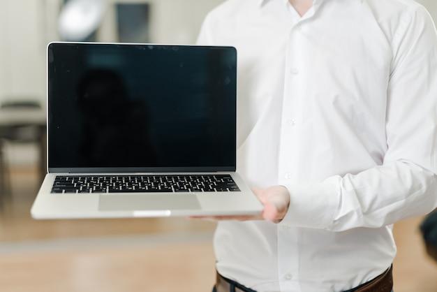 Hombre en la oficina muestra portátil con pantalla en blanco