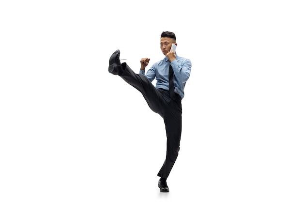 Hombre de oficina practicando taekwondo en pared blanca