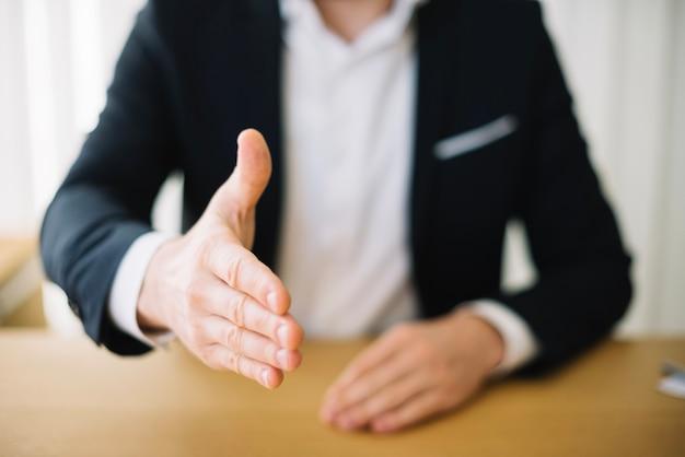 Hombre ofreciendo mano en la oficina