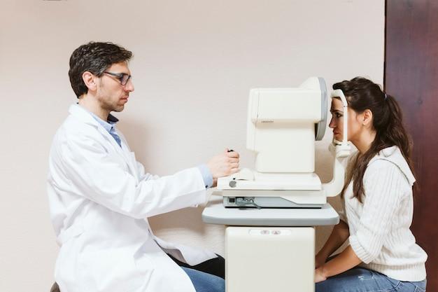 Hombre de oftalmólogo examinando ojos de mujer joven en clínica.
