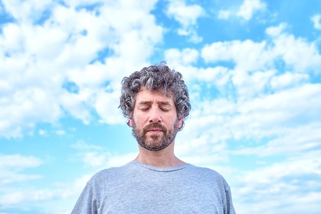 Hombre con los ojos cerrados con un cielo