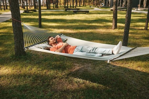 Hombre con los ojos cerrados tumbado en una hamaca en la naturaleza