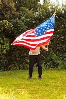 Un hombre ondeando la bandera armenia en el parque