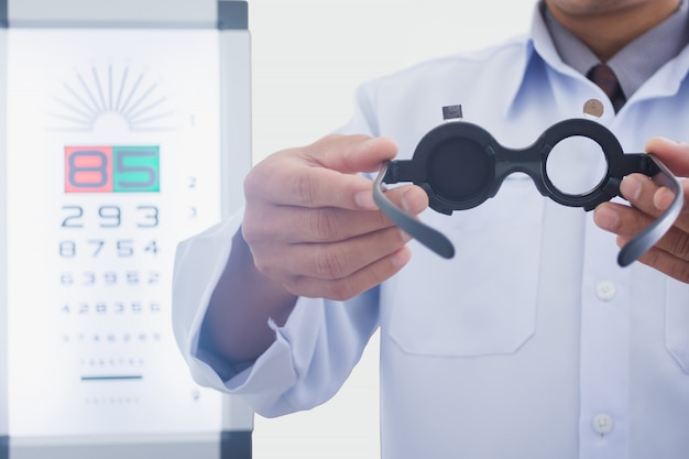 El hombre en la óptica que sostiene los ojos examinó la herramienta para poner en paciente