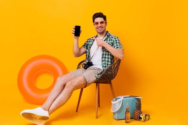 Hombre optimista en camisa verde y pantalón beige y mostrando en su teléfono inteligente. retrato de chico con gafas de sol sentado en una silla con maleta, cerveza, círculo inflable
