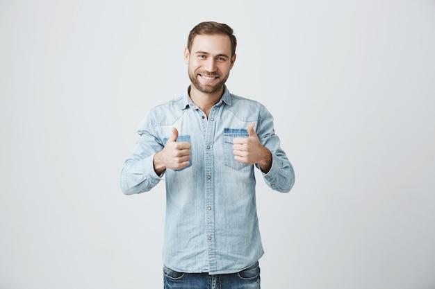 El hombre optimista sonriente muestra el pulgar hacia arriba, aprueba o recomienda