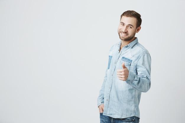 El hombre optimista sonriente muestra el pulgar hacia arriba