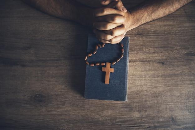 Hombre de oración y cruz de madera en la biblia sobre la mesa