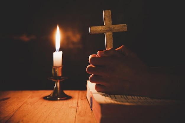 Hombre orando en la biblia en las velas ligeras enfoque selectivo