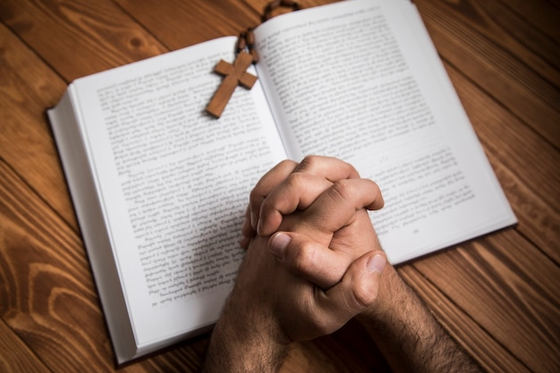 Un hombre orando en un libro sobre una superficie oscura.
