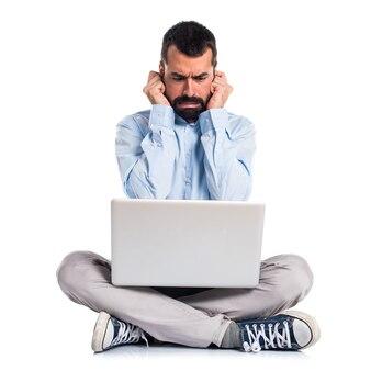 Hombre con el ordenador portátil que cubre sus oídos