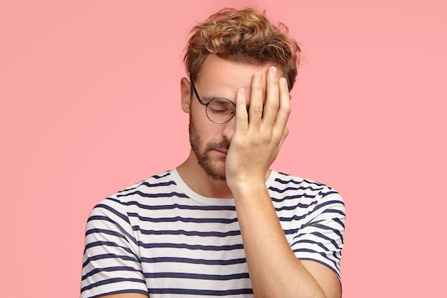 Hombre ordinario rizado cansado con exceso de trabajo mantiene la mano en la cara, cierra los ojos, se siente somnoliento