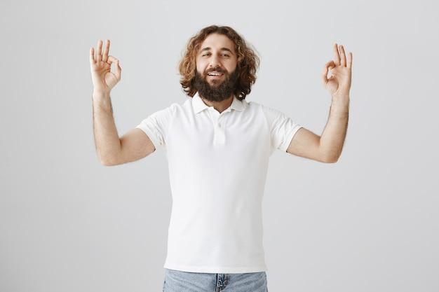 Hombre de oriente medio relajado que muestra un gesto bien, garantiza todo lo bueno