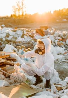Hombre en overoles en la píldora de la basura, investigando
