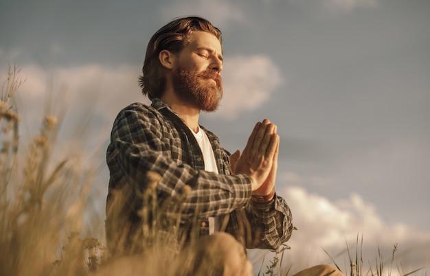 Hombre pacífico sentado en posición de loto en el campo y meditando