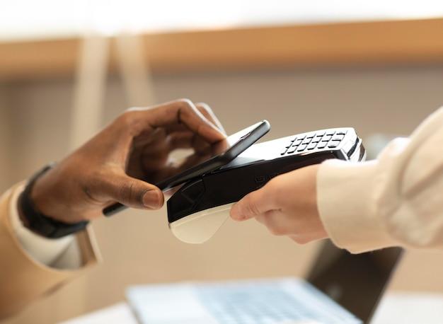 Hombre pagando en la cafetería con su teléfono