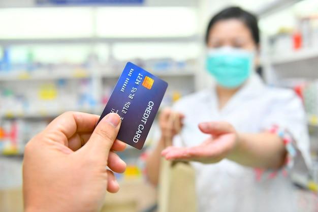Hombre pagando medicamentos con tarjeta de crédito en farmacia farmacia