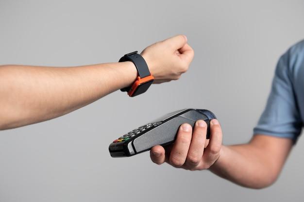Hombre pagando un producto con su reloj inteligente