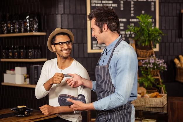 Hombre pagando su café