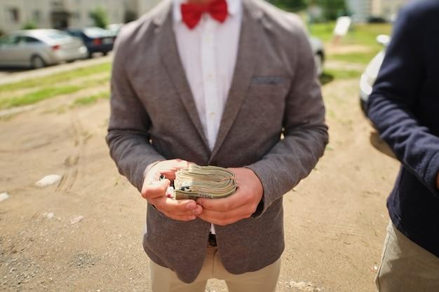 Hombre en una pajarita roja sosteniendo un fajo de dinero