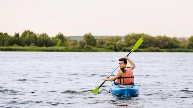 Hombre paleta kayak sobre el lago mirando hacia atrás