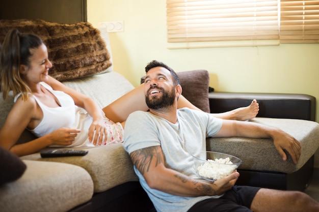 Hombre con palomitas de maíz mirando a su esposa feliz