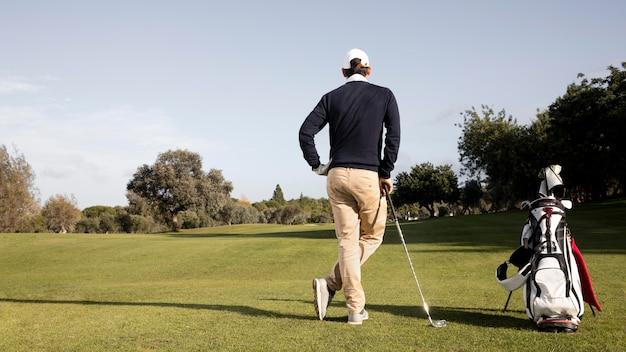 Hombre con palos de golf y espacio de copia en el campo