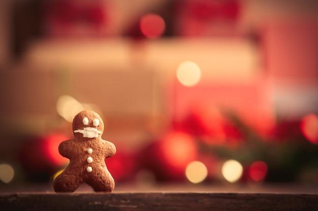 Hombre de pan de jengibre en la mesa con regalos de navidad en el fondo