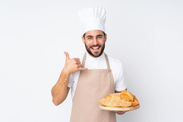 Hombre panadero sosteniendo una mesa con varios panes en la pared blanca haciendo gesto de teléfono