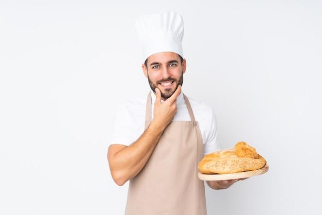 Hombre panadero sosteniendo una mesa con varios panes en la pared blanca pensando en una idea
