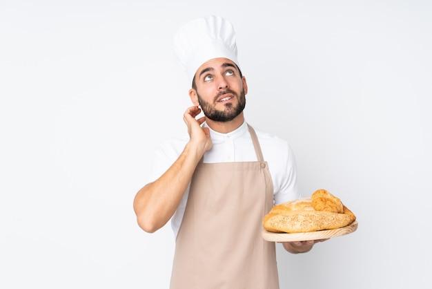 Hombre panadero sosteniendo una mesa con varios panes en la pared blanca pensando