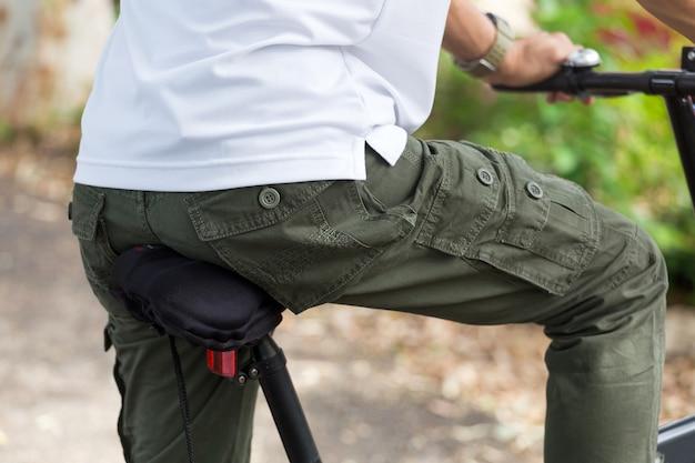 Hombre con pantalones de carga andar en bicicleta en el jardín