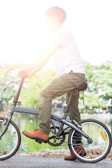 Hombre con pantalones de carga montando una bicicleta en el jardín