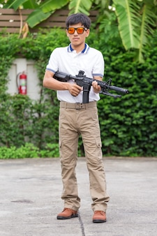 Hombre en pantalones de carga con pistola